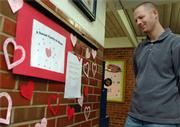 Sunset Hill principal Chris Bay looks over the wall of items needed by the family of one of the school's student's, whose home was damaged in a fire Tuesday in West Lawrence. The wall has several items where people can pick up the suggestion and drop off the item at the school where it will be given to the family.