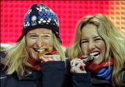 United States snowboarder Hannah Teter, left, bites her gold medal with silver medalist teammate Gretchen Bleiler during the medal ceremony for the Women's Halfpipe Snowboard event at the Turin 2006 Winter Olympic Games in Turin, Italy Monday, February 13, 2006.