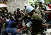 Guatemalan U.N. peacekeepers unsuccessfully try to stop angry supporters of Haitian presidential candidate Rene Preval from entering the upscale Hotel Montana in the Petionville suburb of Port-au-Prince, Haiti, Monday, Feb. 13, 2006, where election officials will announce results of the presidential elections. Protests erupted across the capital as vote counts showed that Preval may have fallen short of the 50 percent needed to win the presidency without a runoff election. The protesters allege the electoral commission is manipulating the vote count to prevent a first-round Preval victory.