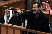 "Former Iraqi president Saddam Hussein gestures in court inside the heavily fortified Green Zone in Baghdad, Iraq  as the latest session of his trial began Monday, Feb. 13, 2006. Saddam Hussein was forced to attend the latest session of his trial Monday, looking haggard and wearing a robe rather than his usual crisp suit as he shouted, ""Down with Bush."" Saddam and his seven co-defendants had vowed not to attend the trial until the return of their lawyers. The defense team are boycotting the proceedings until chief judge Raouf Abdel-Rahman is removed, alleging he is biased against their clients."