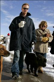 Inmate John Manard, left, is followed by Safe Harbor Prison Dog Program President Toby Young as he walks his dog on the grounds of the Lansing Correctional Facility in Lansing, Kan. in this photo taken Dec, 8, 2005. Manard, in prison for first-degree murder, aggravated robbery and possession of firearms, escaped from prison Sunday. Feb. 12, 2006.  Young, who worked with Manard in the dog rescue program, is missing, and authorities said Monday that she may be with Manard.