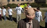 "Brian Azcona, co-president of the Graduate Teaching Assistants Coalition at KU, wears a mask to portray a ""KU bureaucrat"" as GTAs and supporters rally outside of Strong Hall on the Kansas University campus on Tuesday."