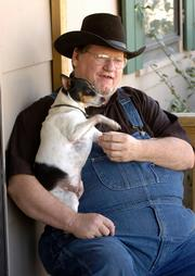 Mike Coffman, of Lecompton, has reached the limit of assistance for his utility bills from ECKAN. Coffman is disabled from injuries resulting from a car accident and cannot work. He is pictured with his dog Butch.