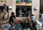 Angry Pakistani protesters demolish the furniture and window of a McDonald's restaurant Tuesday in Lahore, Pakistan.