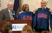 Richard Lariviere, far right, and his wife, Janis, hold up their new Kansas sweatshirts given by Chancellor Robert Hemenway, left, after Lariviere was introduced as the next KU provost.