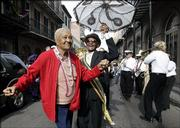Uncle Lionel Batiste, center with umbrella, dances with an unidentified woman who danced in from the sidewalk during the Krew of Cork parade through New Orleans' French Quarter on Friday, Feb 17, 2006. About 400 wine enthusiast and passersby participated in the annual parade.