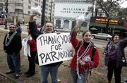 Josh Galjour, left, from New Orleans, holds a sign of appreciation during the Pegasus Parade on Saturday in New Orleans. To the right is Jennifer Cocherham from Houma, La. Saturday's Mardi Gras parades in the Big Easy were shorter and the crowd attendance was lower than in the past.