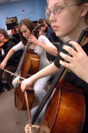 Lawrence High School sophomores and cello players Ellen Hernly, left, and Anna Cook rehearse with the LHS orchestra. The Lawrence school district will send five ensembles to the prestigious Kansas Music Educators Assn. annual convention. They'll perform Friday in Wichita.