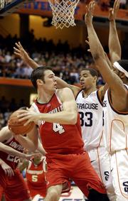 Louisville's David Padgett, left, is pressured by Syracuse's Terrence Roberts (33) and Darryl Watkins during Saturday's game in Syracuse, N.Y. Louisville announced Tuesday that Padgett would miss the rest of the season because of a knee injury.