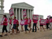 Planned Parenthood advocates who support a woman's right to an abortion march in front of the U.S. Supreme Court in July. Justices have agreed to consider reinstating a ban on late-term abortions.