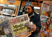 "A vendor reads a newspaper with its front page showing Bosnian Serb war crimes fugitive Gen. Ratko Mladic, at his newsstand in the Serbian capital, Belgrade. Mladic, charged with genocide for some of the worst atrocities of the Bosnian war, has been located and authorities are negotiating his surrender, senior state security officials said Tuesday. The headline reads ""Mladic surrounded."""