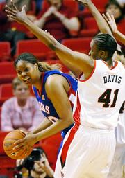 Kansas University's Crystal Kemp, left, looks to pass around Texas Tech's LaToya Davis in the Jayhawks' 62-50 loss. KU fell to the Red Raiders on Wednesday in Lubbock, Texas.