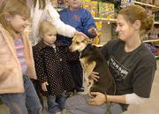Gracie Bessey, left, and Sophie Bessey, of Shawnee, pet Kasi, a beagle mix, held by Jessica Kirby, of the Safe Harbor Prison Dog program, during a pet adoption in Shawnee. In an interview this week, Kirby said she warned Safe Harbor founder Toby Young about Lansing Correctional Facility inmate John Manard being manipulative. Young is thought to have aided in Manard's escape from Lansing on Feb. 12.
