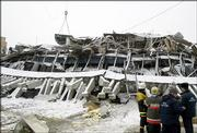 Rescuers stands in front of the wreckage of the collapsed market in Moscow, Thursday, Feb. 23, 2006. The concave, snow-covered roof of a three-decade-old Moscow market collapsed early Thursday, killing at least 35 people and forcing rescuers to clear away concrete slabs and metal beams to reach possible survivors trapped in the wreckage, officials said.