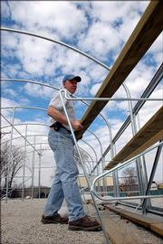 Parks and Recreation employee Curt Talken assembles a new greenhouse at 11th Street and Haskell Avenue. Next week city commissioners will consider a $90,000 proposal to revamp the city's landscaping process in downtown Lawrence. The plan calls for more plantings that bloom throughout the growing season.