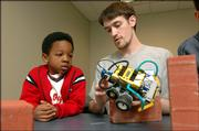 Ross Kazadi, 6, a student at Raintree Montessori School, learns how Kansas University senior Dustin Herschberger operates his robot made of Legos. The robot was one of many devices on display Friday morning at the annual Engineering Expo at KU.