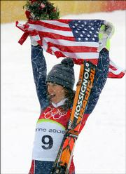 Julia Mancuso of the United States celebrates after winning gold during the flower ceremony for the Women's Giant Slalom at the Turin 2006 Winter Olympic Games in Sestriere Colle, Italy, Friday, Feb. 24, 2006.