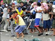 "Protesters flee as riot police chase them away during dispersal operation when the protesters tried to march towards the ""People Power"" monument for an anti-Government rally Friday Feb. 24, 2006 at suburban Quezon city,  northeast of Manila. The military tried to quash a possible coup attempt Friday, arresting an army general accused of involvement in the plan and urging soldiers not to get involved in politics by joining demonstrations calling for President Gloria Macapagal Arroyo to quit."