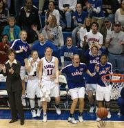 Kansas coach Bonnie Henrickson, left, and players on the KU bench celebrate a late basket from Sharita Smith in the Jayhawks' 81-71 victory over Missouri. Smith's bucket made it 61-all in regulation, and KU went on to win in overtime Saturday in Allen Fieldhouse.