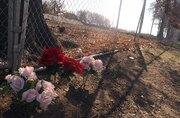 Three sets of flowers rest by the chain link fence where the Boardwalk Apartment building burned last October. The flowers are in memory of the three people who died in the blaze.