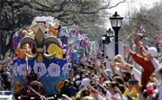 Crowds along Napoleon Avenue cheer as the Krewe of Toth Mardi Gras parade rolls by Sunday in the Uptown area of New Orleans.