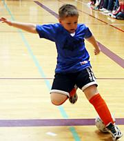 Dragon Philip Foster sticks out his foot to stop the ball from rolling out of bounds. The Rookie boys league Dragons dominated the Saturday game against the Tigers at the East Lawrence Center. One of Futsal's main objectives is to improve players' ball handling abilities.