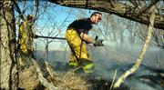 A Kanwaka Township firefighter battles a grass fire near North 1250 Road just west of Clinton Lake on Monday.