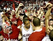 Oklahoma guard David Godbold (15) along with other players and fans celebrate after beating Oklahoma State 67-66 in an NCAA basektball game Monday, Feb. 27, 2006 in Norman, Okla.