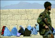 A soldier of the Afghan National Army stands guard as the relatives of prisoners wait outside the Policharki Prison in Kabul, Afghanistan , Monday, Feb. 27, 2006. Security forces with tanks and heavy guns surrounded Kabul's main prison Monday, as authorities sought to resume negotiations with rioting prisoners but warned they could use force.