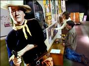 "With the protection of a John Wayne cardboard cut-out, Morgan Shortle and Ron Seeger add final touches to the exhibit, ""Blazing Guns and Rugged Heros -- Kansas in the Westerns,"" at the Kansas Museum of History in Topeka, Kan., Wednesday, Jan. 25, 2006. The exhibit, which opened Saturday, Jan 27, and runs through September, features posters and items from popular movie and television westerns set in Kansas."