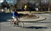 A bicycler rides through a traffic calming circle at 17th Street and New Hampshire St. The city recommended constructing two similar  devices on 13th Street between Connecticut St. and Haskell Avenue. New traffic circles, speed bumps and other traffic calming devices are slated for all parts of town.But the city hasn't figured out how to fund them yet.