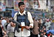A militiaman loyal to radical Shiite cleric Muqtada al-Sadr stands guard in the Shiite district of Sadr city, in Baghdad, Iraq, Friday, March 3, 2006. Shiite militiamen helped police check cars and patrol the area in a bid to avert attacks during midday prayers Friday when large numbers of Muslims congregate for the most important service of the week.