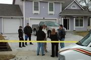 Investigators, including Baldwin Police Chief Mike McKenna, center in hat, and Douglas County Dist. Atty. Charles Branson, far right, discuss a shooting that occurred early Saturday at a Baldwin residence. Alvin Sanchez, 27, of Olathe, was shot and died later in the day. A 25-year-old suspect was in custody Saturday in Oklahoma, according to the Oklahoma Highway Patrol.