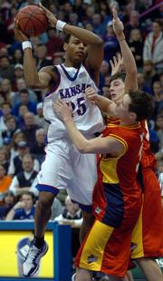 Kansas University's Brandon Rush - shown here driving against Iowa State's John Neal - on Tuesday was named to the AP's All-Big 12 second team and was tapped player of the year in District VI.