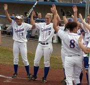 Kansas University softball players Betsy Wilson, left, and Jessica Moppin celebrate with teammates after Heather Stanley's home run in the third inning against Missouri State. The Jayhawks swept the Bears in a home-opening doubleheader on Wednesday at Arrocha Ballpark.