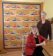 Some of Kansas University basketball's biggest stars are helping the Social Service League this year in its annual effort to buy shoes for Lawrence children. The league will be auctioning a quilt signed by 41 current and former KU basketball players and coaches on eBay. The auction is set to begin at 6 tonight. With the quilt Wednesday are designer and quilter Barbara Brackman, left, and quilter Deb Rowden.