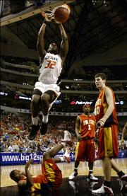 Iowa State's Will Blalock, bottom, Ross Marsden, right, and Curtis Stinson, center bottom, look on as Oklahoma State's David Monds (32) dunks over them in the second half of the Big 12 Men's Basketball Championship first round game in Dallas, Thursday, March 9, 2006.  Oklahoma State defeated Iowa State, 79-70.