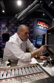 Disc jockey Nico Jones gestures while working at the Latino 96.3 radio studio in Los Angeles Friday, Jan. 6, 2006. The station has an English format targeting Hispanics.