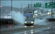 A car splashes water and mud while driving East on North Frontage Road by Interstate 20/59 during a heavy rain storm in Meridian, Miss., Thursday, March 9, 2006. Wind gusts were reported as high as 85 mph during the storm in Mississippi.
