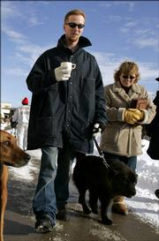"Inmate John Manard, left, is followed by Safe Harbor Prison Dog Program President Toby Young as he walks his dog on the grounds of the Lansing Correctional Facility in Lansing, Kan., Dec, 8, 2005. Proclaiming his deep love for ""an angel"" and continuing to deny that he was a violent criminal, Manard said Wednesday, March 8, 2006, he was solely responsible for his Feb. 12, 2006, escape in a dog crate from this Kansas state prison. In a four-page letter to television station KCTV in Kansas City, Manard said he loved Young, a 48-year-old married mother of two, ""more than life"" and he planned the escape from Lansing Correctional Facility so he could be with her. KCTV said Manard&squot;s sister verified that the handwriting was her brother&squot;s."