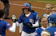 Kansas University's Jessica Moppin is congratulated after her home run against Minnesota. The Jayhawks split a doubleheader Friday at Arrocha Ballpark in the Jayhawk Classic, beating Minnesota, 6-3, but falling to Eastern Michigan, 2-1.