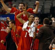 The Nebraska bench including guard Jason Dourisseau goes wild after the Huskers defeated Oklahoma Friday night in Dallas.