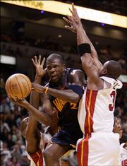 Golden State Warriors' Jason Richardson goes to the basket between Miami Heat's Dwyane Wade, right, and Gary Payton, left, during the first quarter of an NBA basketball game Friday, March 10, 2006, in Miami.