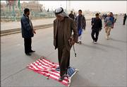 Iraqi Shiite Muslims walk over a U.S. flag as they go to Friday prayers in Shiite district of Sadr city, in Baghdad, Iraq, Friday, March 10, 2006. President Jalal Talabani issued a decree Friday that orders Iraq's new parliament to hold its first session on March 19. The United States wants to leave behind a strong central authority and has made that a pre-condition for its hopes to begin drawing down American forces this summer.