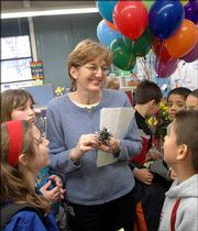 Fifth-grade students at Schwegler School surround teacher Debby Cummings after they presented her with a balloon bouquet. This week Cummings was selected as the 2006 Lawrence Elementary Teacher of the Year.