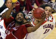 Florida's Joakim Noah, right, battles South Carolina's Renaldo Balkman for the ball. The Gators won, 49-47, to take the SEC tournament title Sunday in Nashville, Tenn.