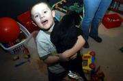 Ethan Folks, 5, enjoys a moment with his dog in his play room. Ethan's mom, Jacqui Folks, along with Rebecca Dority, are searching for members for an autism support group in Eudora.
