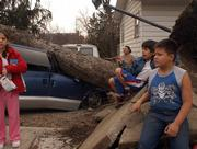 A storm with winds of at least 70 mph caused significant damage across Lawrence on Sunday morning. From left, Myra Leclaire, Javier Alva, 9, and Bruce Whiteman, 8, survey the damage after an uprooted tree smashed the family's minivan in the driveway of their home near 23rd Street and Haskell Avenue.