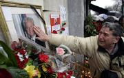 A supporter of former Serbian leader Slobodan Milosevic touches Milosevic's photograph Sunday in front of the Socialist Party of Serbia's headquarters in downtown Belgrade. Preliminary autopsy results show Milosevic died of a heart attack Saturday while awaiting trial at The Hague, Netherlands.