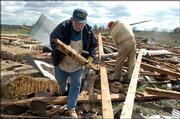 Don Troughton, of Overland Park, and Bruce Evans, of Lawrence, help clean up sheds at Pendleton's Country Market, 1446 E. 1850 Road, that were damaged in Sunday's storm.